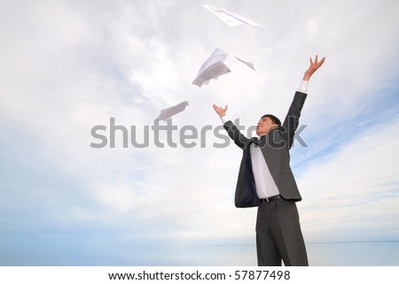 young guy in a business suit with joy throwing papers in the sky