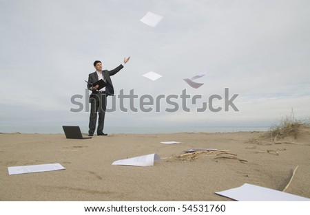 young guy in a business suit with joy throwing papers on the beach - stock photo