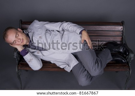 Young guy in a suit sleeping on a bench - stock photo
