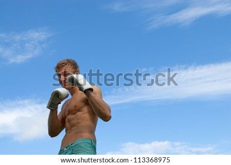 Young guy in boxing gloves, on blue sky background.