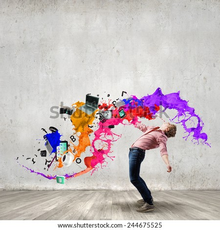 Young guy in casual evading from colorful splashes - stock photo