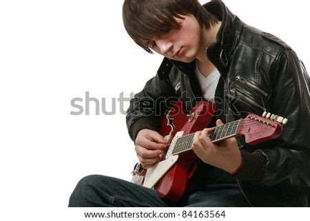 Young guy in leather jacket playing electric guitar - stock photo