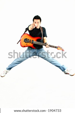 Young guy jumping with guitar.