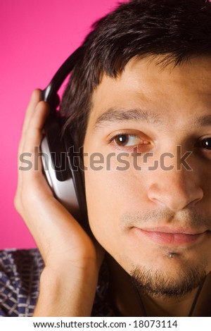 Young guy listening music with headphones, pink background - stock photo