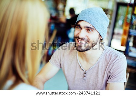 Young guy looking at his girlfriend while listening to her - stock photo