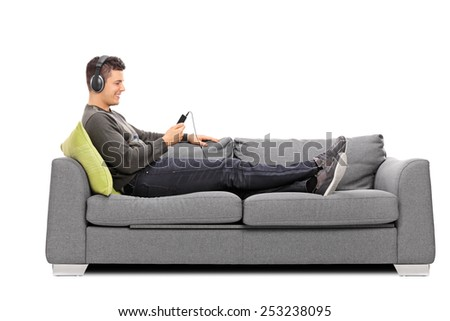 Young guy lying on sofa and listening to music on his cell phone isolated on white background