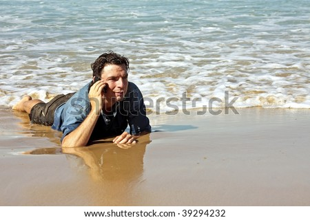 Young guy making a phonecall in the water from the ocean