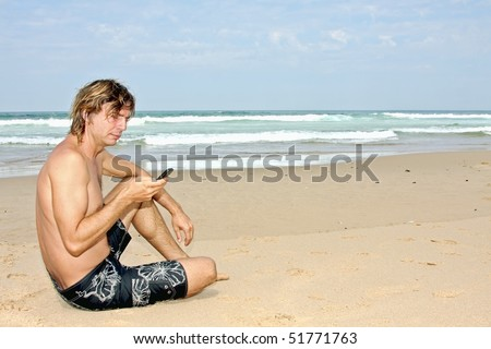 Young guy making a text message sitting on the beach - stock photo