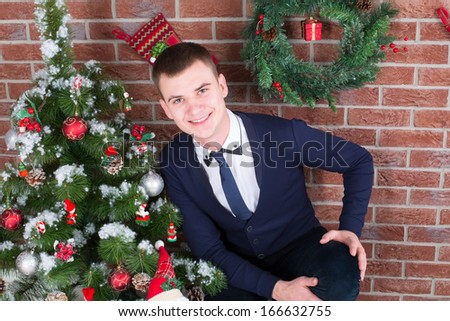 young guy next to a Christmas tree with gifts