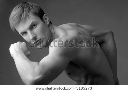 young guy of an athletic constitution does sports exercises, close up