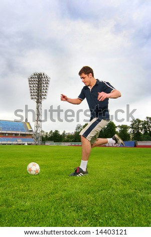young guy playing football on stadium