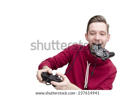 Young guy playing video game funny holding one joystick in his mouth and one in his hands. Addicted to video games - stock photo