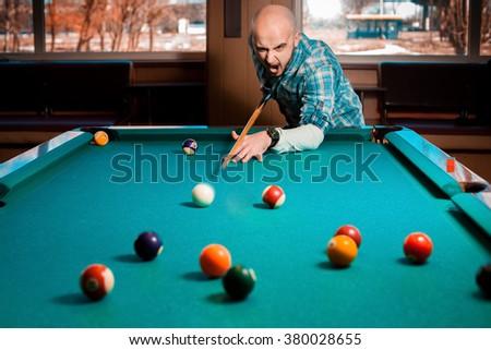 young guy plays pool billiard. American pool billiard. Pool billiard game. Billiard sport concept. - stock photo