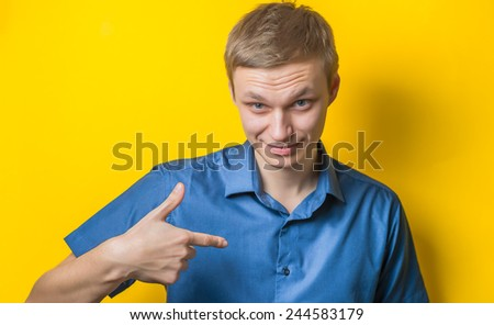 Young guy pointing to himself with a questioning look as if to say Who Me?  Isolated on white. - stock photo