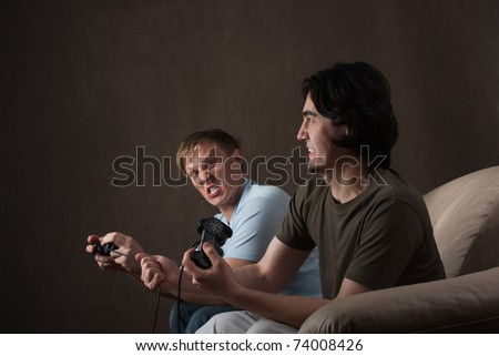 young guy pulling friend's joystick cord while playing video games on gray background - stock photo