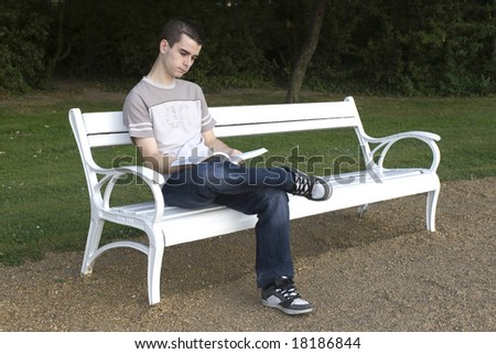 Young guy reads a book. - stock photo