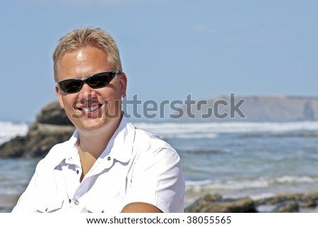 Young guy smiling at the atlantic ocean