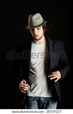 Young guy standing against a black background - stock photo