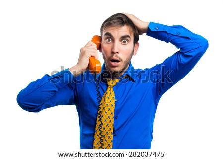 young guy talking on landline orange , surprised, isolated on white background - stock photo