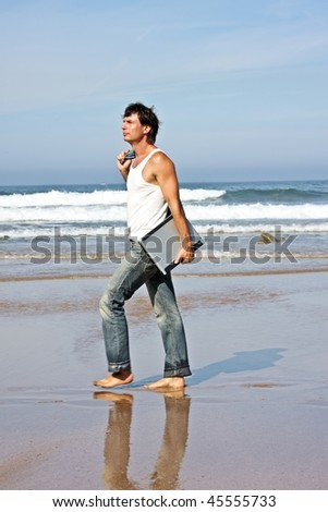 Young guy walking with his laptop on the beach - stock photo