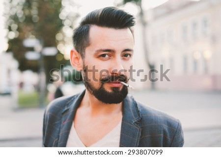 young guy with a beard and a mustache in a suit posing on the street in the sunlight and smoke a cigarett