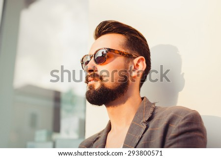 young guy with a beard and mustache with sunglasses and jacket posing on the street the sun shines, vintage man, fashion men, hipster street casual - stock photo