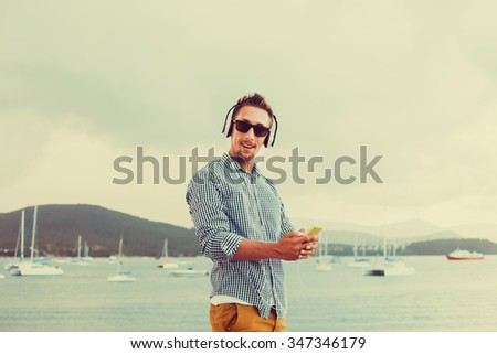 young guy with a beard in sunglasses shirt and shorts listening to music in headphones on a smartphone on the pier near,street style,casual outfit,listen music,mans style,fashion,style,coolest  - stock photo