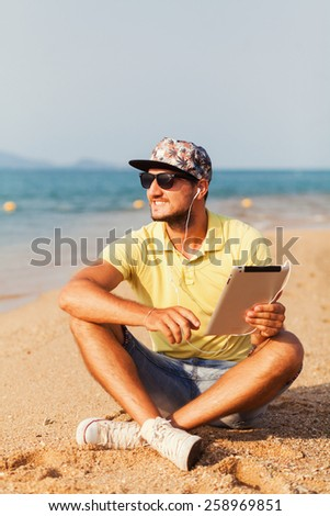 Young guy with a beard wearing glasses wearing a yellow T-shirt and shorts sits on a sandy ocean beach and working on laptop - stock photo