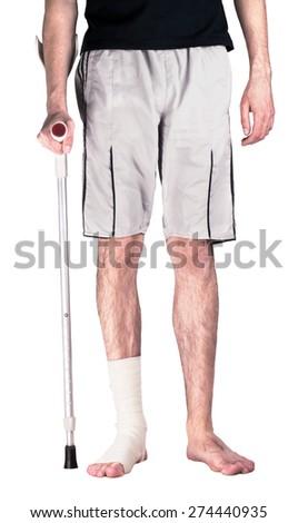 Young guy with bandaged injured leg on crutches - stock photo