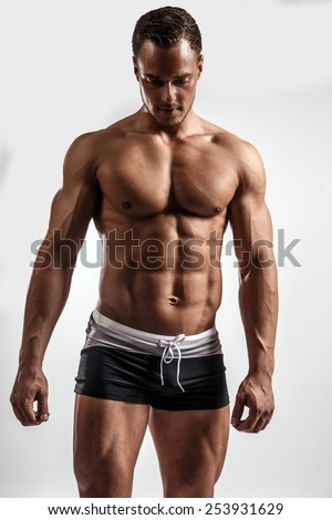 Young guy with great body anatomy in black swim shorts possing in studio. Isolated on white background.
