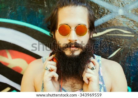 Young guy with long hair mustache and beard listening to music with headphones,young guy with a beard and mustache with glasses in the sunlight, fashion man, style, vintage style, retro men,stylish - stock photo
