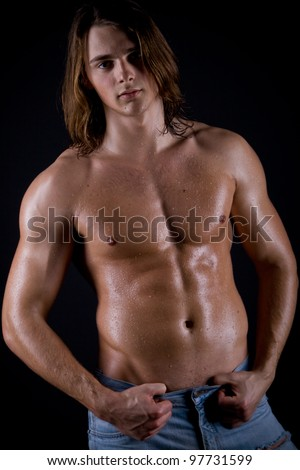 young guy with long hair, naked and wet with a muscular torso against a dark background - stock photo