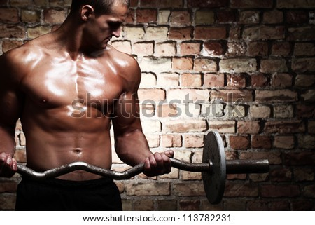 Young guy with muscular body with barbell over brick wall