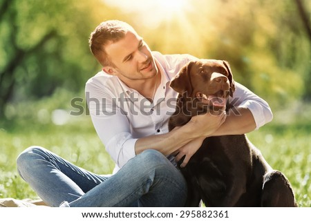 Young guy with retriever on walk in summer park - stock photo