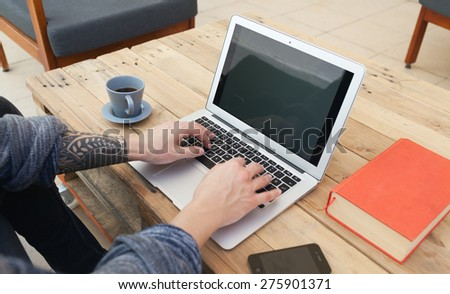 young guy with tattoed arm using a laptop - stock photo