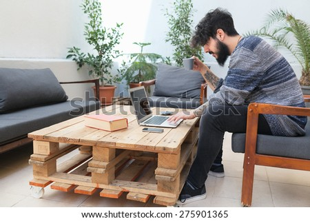young guy with tattooed arm using a laptop  - stock photo
