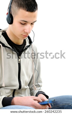 Young guy with the beard, sitting on a stool, listening to music with headphones from a smartphone, photo on white background. - stock photo