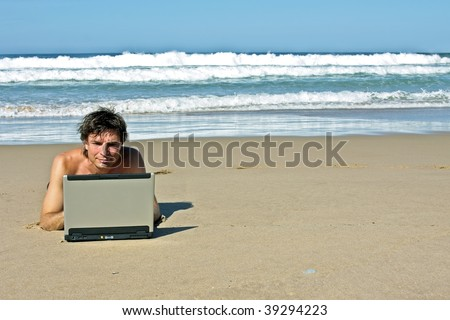 Young guy working on his laptop on the beach - stock photo