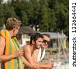 Young guys holding glasses talking at beach - stock