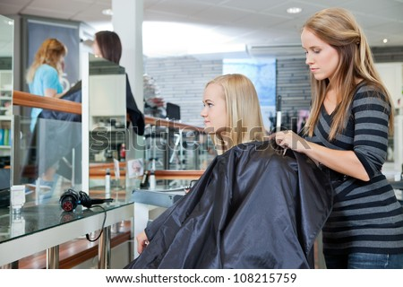 Young hairdresser making preparation before giving a haircut to female customer at parlor - stock photo