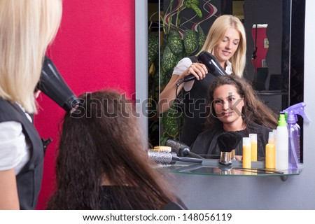 young hairstylist drying woman's hair in beauty salon - stock photo