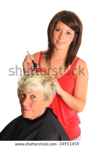 Young hairstylist putting highlights in a customers hair. - stock photo