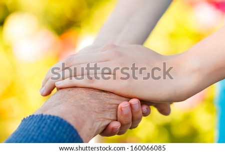 Young hand holding an elderly man's hand - conceptual picture. - stock photo