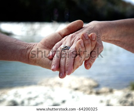 Young hand supporting old hand-helping elderly people concept - stock photo