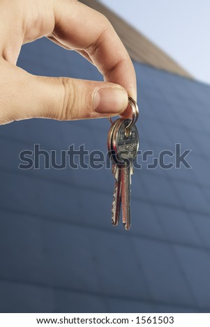 Young hand with keys in front of business office building - stock photo