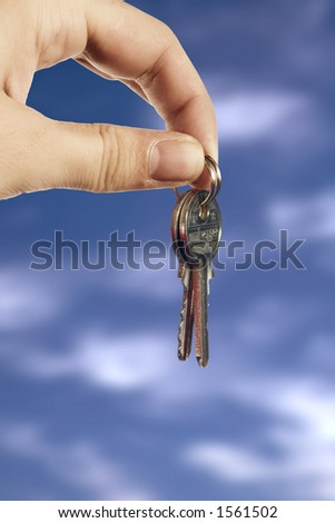 Young hand with keys on clouds background - stock photo