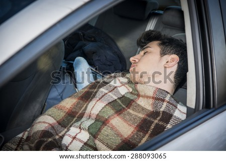 Young handosme man sleeping inside his car, exhausted, tired