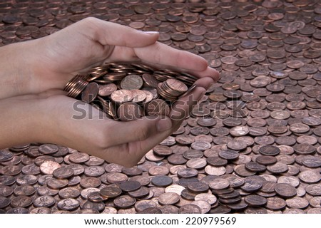 young hands cupped together holding pennies over a background of pennies - stock photo
