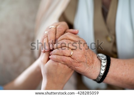 Young hands holding an old hands - stock photo
