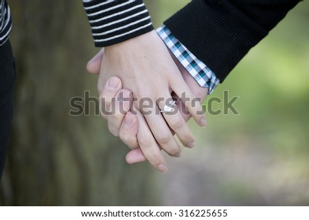 Young hands holding with an engagement ring on a sunny day.